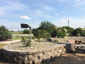 Picture of  the Friends of the Stone Arch Trail's flower mound renovation project under the Agricultural Symbol Sculpture.